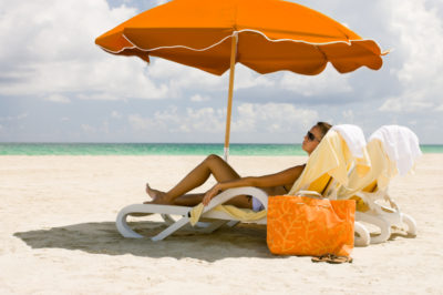 woman relaxing in recliner under the umbrella at a beach in Miami, Florida